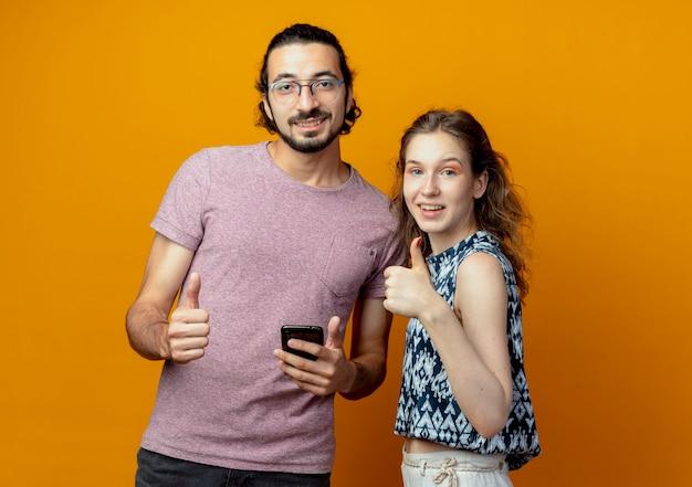 Casal jovem olhando para a câmera sorrindo, feliz e positivo, mostrando os polegares em pé sobre um fundo laranja