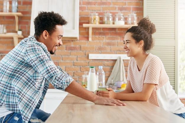 Casal jovem ou família sentam-se juntos na cozinha, têm uma conversa agradável, bebem leite, discutem seus planos para os fins de semana