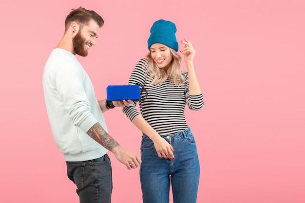 Casal jovem ouvindo música no alto-falante sem fio, vestindo roupas elegantes e legais, sorrindo, posando em rosa