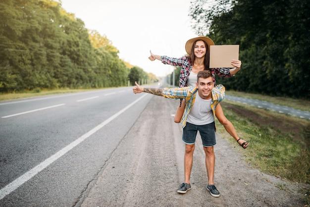 Casal jovem pedindo carona com papelão vazio