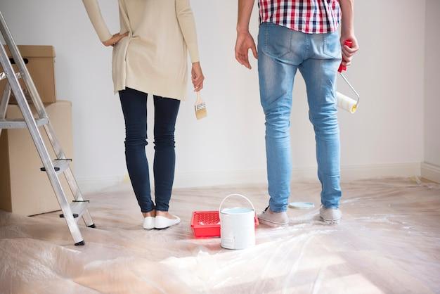 Casal jovem pintando paredes