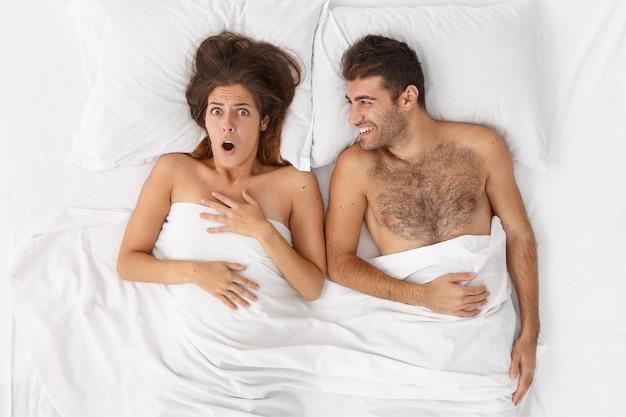 Casal jovem recém-casado acorda de manhã. mulher assustada se lembra de algo surpreendente, marido alegre deitado perto de uma cama confortável sob o lençol branco. pessoas, casa, relacionamento, conceito de cama