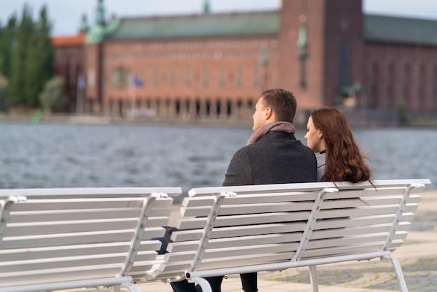 Casal jovem relaxando em um banco, apreciando o pôr do sol enquanto contempla a vista do mar e de edifícios históricos em uma cidade com espaço de cópia