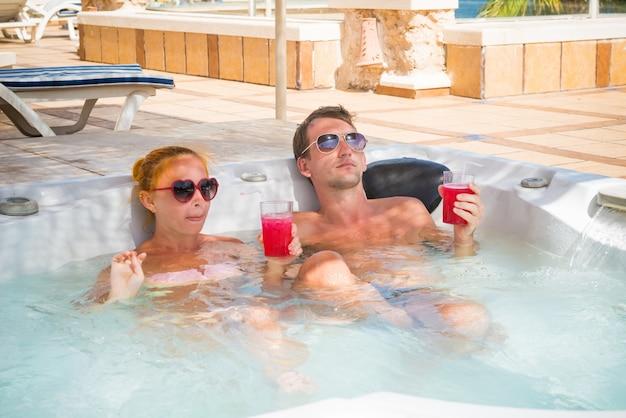 Casal jovem relaxando na piscina jacuzzi