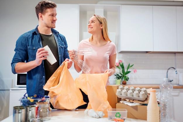 Casal jovem responsável, colocando papel e plástico vazio em sacos de lixo