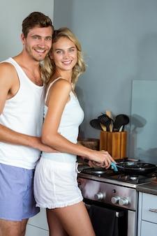 Casal jovem romântico a cozinhar comida na cozinha em casa