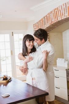 Casal jovem romântico, abraçando um ao outro na cozinha