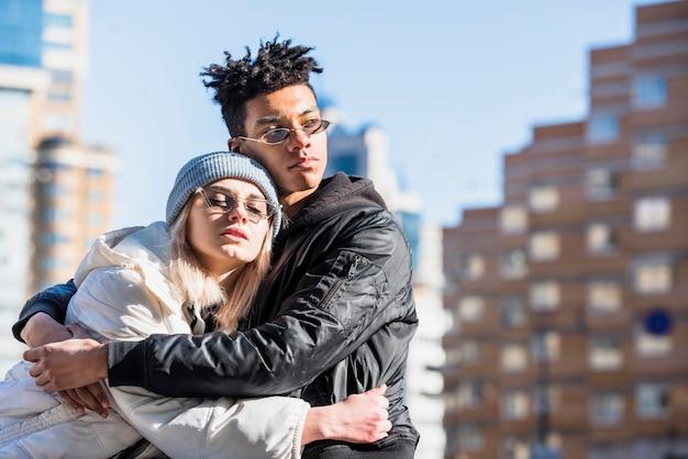Casal jovem romântico, abraçando uns aos outros na cidade