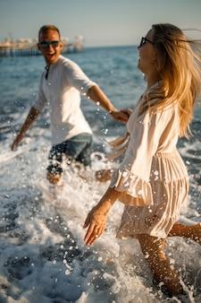 Casal jovem romântico apaixonado juntos na areia caminha ao longo da praia do mar mediterrâneo. férias de verão em um país quente. foco seletivo