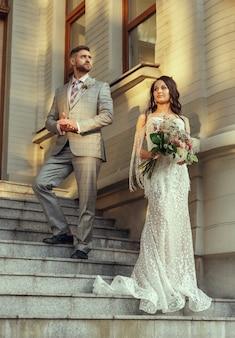 Casal jovem romântico caucasiano celebrando seu casamento na cidade. concurso noiva e noivo nas ruas da cidade moderna. família, relacionamento, conceito de amor. casamento contemporâneo. feliz e confiante.