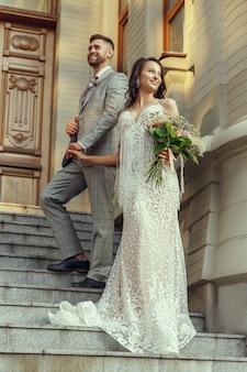 Casal jovem romântico caucasiano celebrando seu casamento na cidade. concurso noiva e noivo nas ruas da cidade moderna. família, relacionamento, conceito de amor