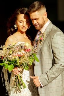 Casal jovem romântico caucasiano celebrando seu casamento na cidade. ternos noivos nas ruas da cidade moderna no verão. família, relacionamento, conceito de amor. casamento contemporâneo.
