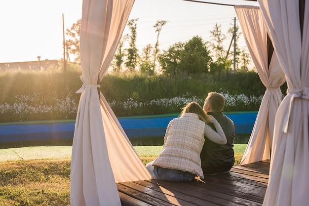 Casal jovem romântico curtindo um encontro sentado em um abraço apertado em um banco de parque com vista para um lago, vista de trás