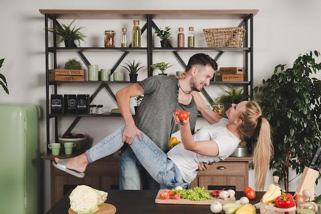 Casal jovem romântico em pé atrás do balcão da cozinha