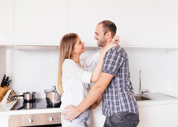 Casal jovem romântico em pé na cozinha olhando um ao outro