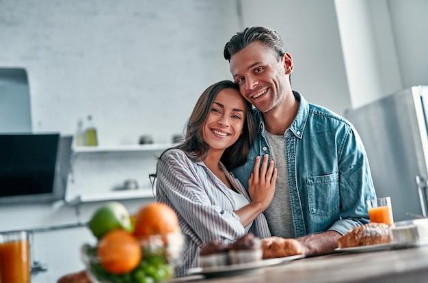 Casal jovem romântico na cozinha se preparando para o café da manhã. mulher jovem e atraente e um homem bonito estão gostando de passar algum tempo juntos em pé na cozinha moderna leve.