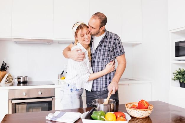 Casal jovem romântico, preparando a comida na cozinha
