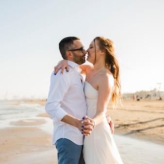Casal jovem romântico, segurando a mão do outro, apreciando na praia