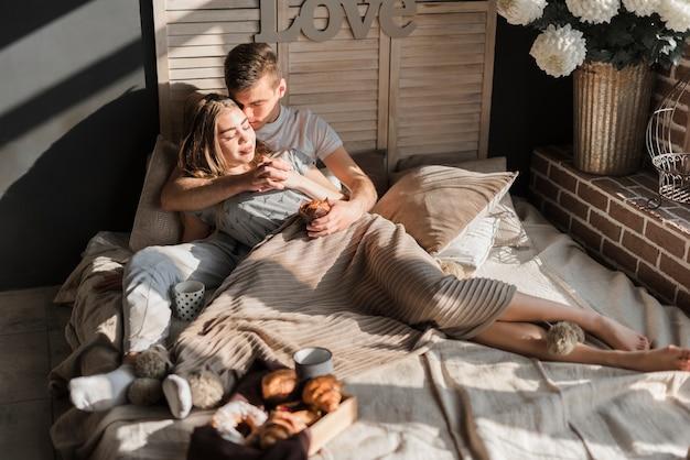 Casal jovem romântico, segurando a mão do outro com café da manhã na cama