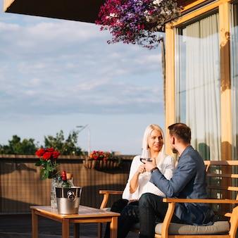 Casal jovem romântico sentado no restaurante no terraço apreciando a bebida