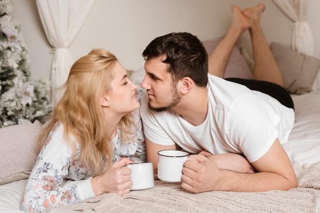 Casal jovem romântico tomando café na cama