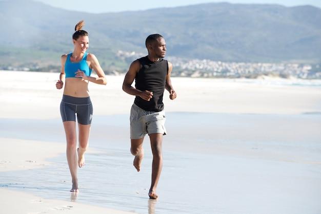 Casal jovem saudável, correndo ao longo da praia