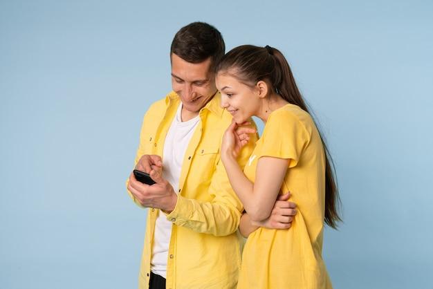 Casal jovem se abraçam, olham alegremente para o telefone móvel, felizes em ver fotos comuns, satisfeitos com a boa conexão sem fio, resistem ao azul