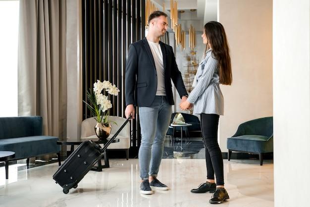 Casal jovem se despedindo em pé no saguão do hotel antes de o homem sair