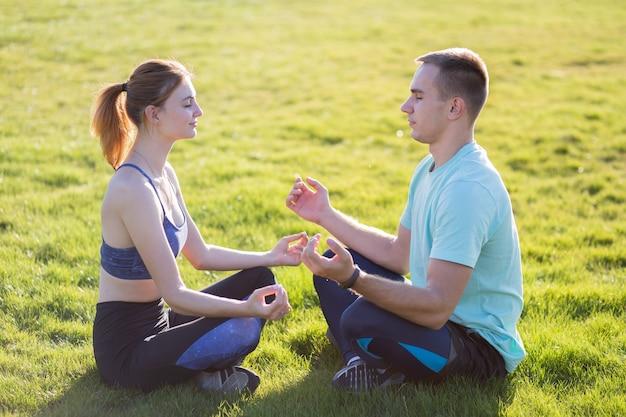 Casal jovem se divertindo ao ar livre. homem e mulher meditando juntos fora no campo com grama verde ao nascer do sol.