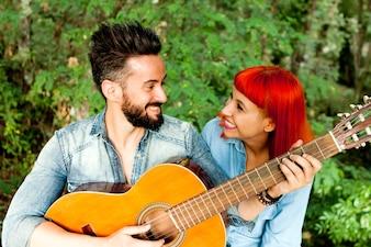 Casal jovem se divertindo com guitarra no parque.