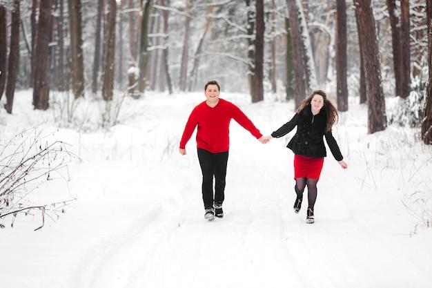 Casal jovem se divertindo com neve na floresta de inverno. homem e mulher, desfrutando de um passeio.