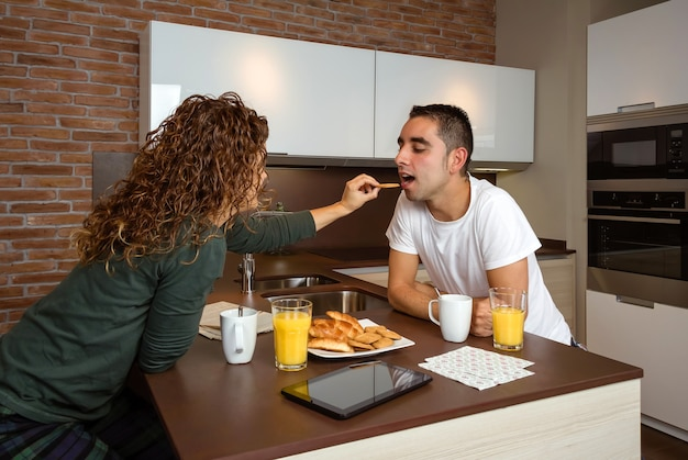 Casal jovem se divertindo enquanto toma o café da manhã na cozinha, alimentando-se