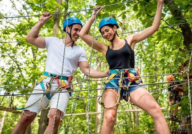 Casal jovem se divertindo no parque de corda aventura