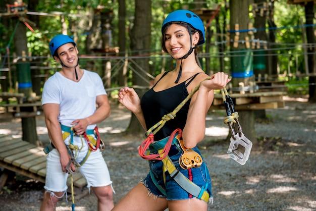 Casal jovem se divertindo no parque de corda de aventura.