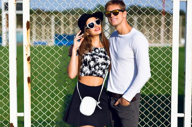 Casal jovem se divertindo no verão, abraços, emoções, usando roupas elegantes em preto e branco e óculos escuros