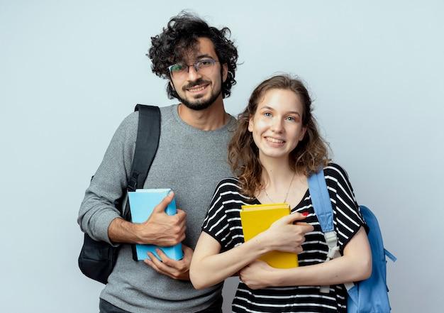 Casal jovem segurando livros, olhando para a câmera, sorrindo, feliz e positivo, em pé sobre um fundo branco