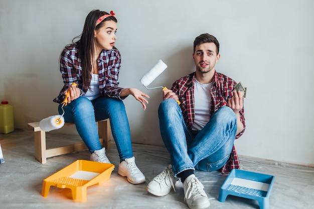 Casal jovem segurando os rolos de pintura e sorrindo um ao outro enquanto descansava durante a reparação