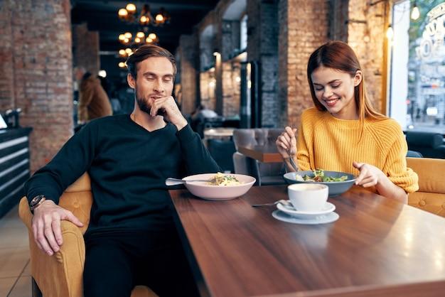 Casal jovem sentado em um restaurante conversando namoro