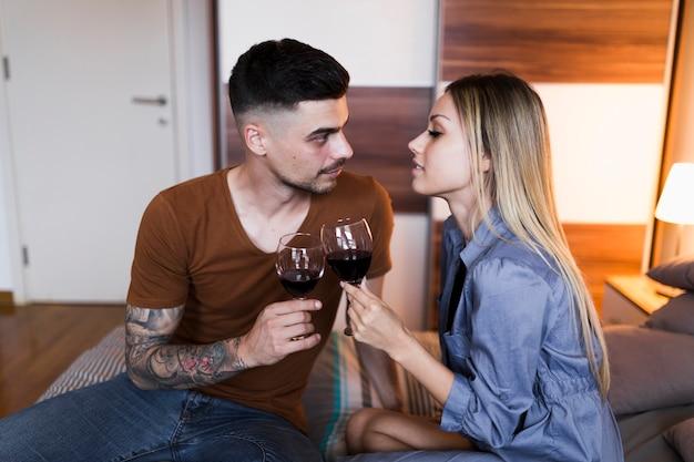 Casal jovem sentado na cama, brindando vinho