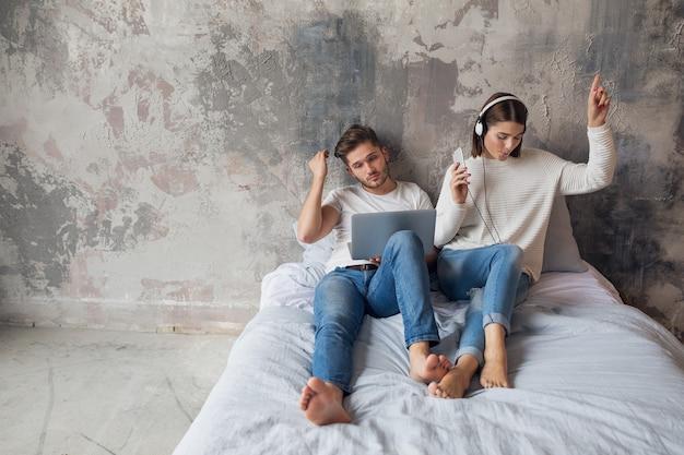 Casal jovem sentado na cama em casa com roupa casual, homem ocupado trabalhando como freelance em um laptop, mulher ouvindo música em fones de ouvido, passando tempo juntos
