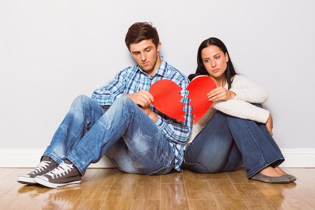 Casal jovem sentado no chão com coração partido