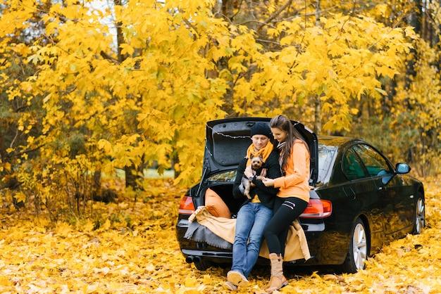 Casal jovem sentado no porta-malas aberto de um carro preto