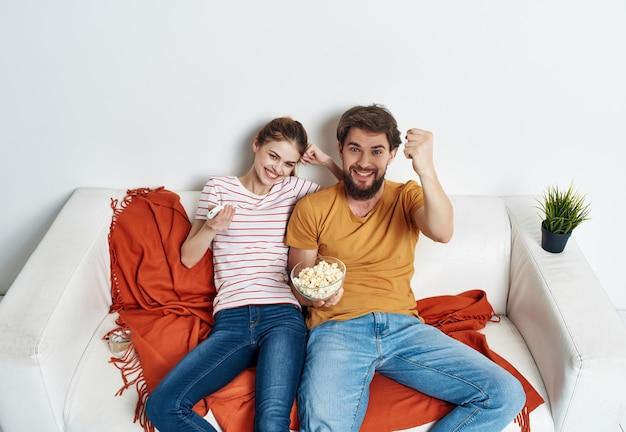 Casal jovem sentado no sofá pipoca assistindo filme em família