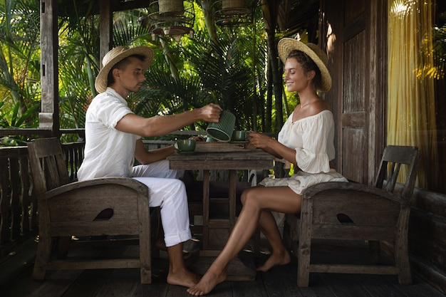Casal jovem sentado no terraço e bebendo café ou chá durante o dia ensolarado de verão Foto Premium