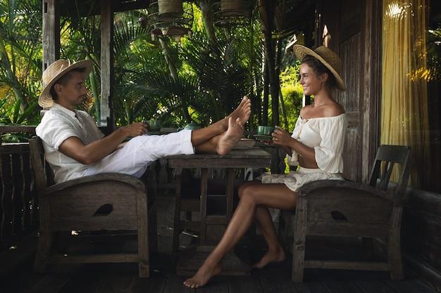 Casal jovem sentado no terraço e bebendo café ou chá durante o dia ensolarado de verão
