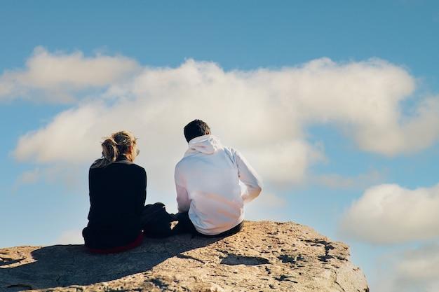 Casal jovem sentado no topo de um penhasco sob um céu nublado