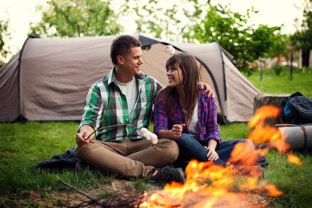 Casal jovem sentado perto de uma fogueira e torrando marshmallow