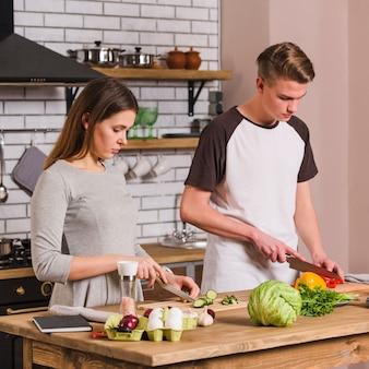 Casal jovem sério cozinhar alimentos