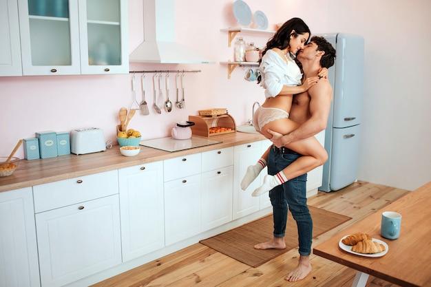 Casal jovem sexy em itchen. ele a segura com as mãos. modelo abraça o homem. eles beijam.