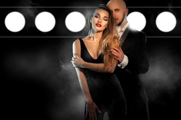 Casal jovem sexy em terno preto abraços e olham para a câmera no estúdio na parede de fumaça escura